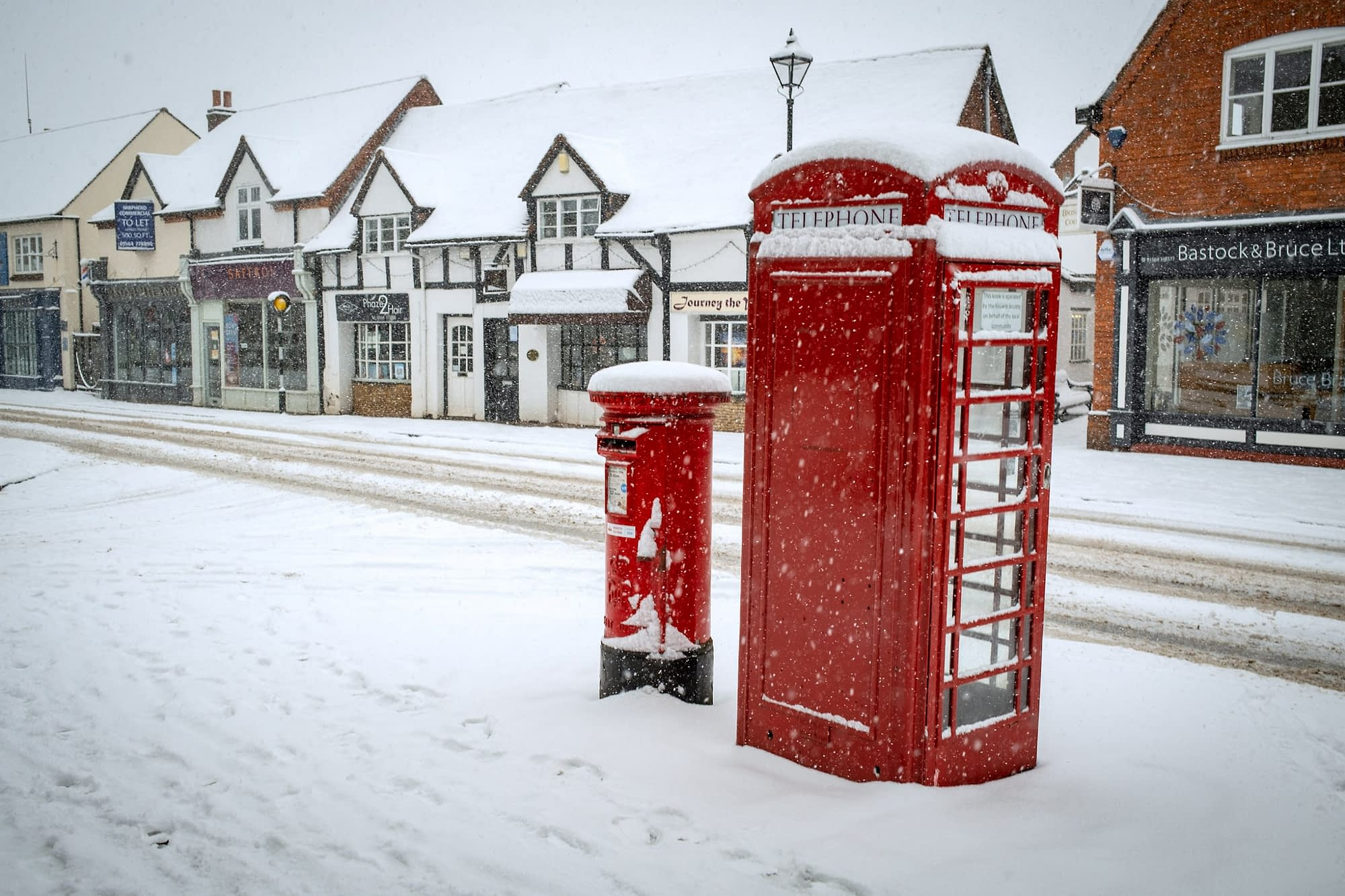 Red post and telephone box in the snow